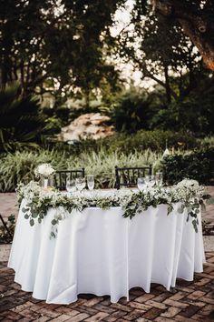Baby's breath and silver dollar eucalyptus garland design for a half moon sweetheart table.