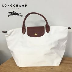 "Longchamp Medium Le Pliage tote bag. 100% Authentic!! Beautiful and classic bag!!  Only used twice, has one light mark near the top that is no visible at all, please look at the picture I point with a arrow... other than that minimal and normal sign of wear. No tear or stain at all.  Longchamp Medium white Le Pliage tote short straps bag. Dimensions are 18"" X 11"" X 8"" short leather straps drop 5"" Comes from smoke free home. Longchamp Bags Totes"