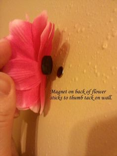 Use a simple flat metal pushpin in the wall and a flower with a magnet hot-glued to the back. Easy-peasy! And easy to change out for different looks.