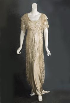 The bodice, skirt front, and fishtail train are embroidered with loops of sparkling crystal beads. Made from champagne colored satin with a draped overdress of very fine hand-assembled tape lace, the majestic gown will make an indelible impression on the viewer.