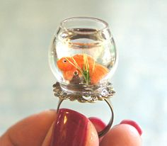 This ring features a miniature glass fish bowl adorned with a handmade goldfish sculpted from polymer clay. the glass fishbowl is securely attached to a bronze filigree adjustable ring that fits most