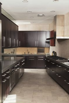 This dark wood galley kitchen combines light beige stone in the floors and backsplash with a more modern stainless steel in the countertops.