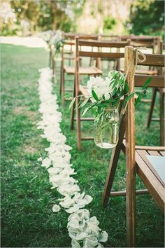 mason jar floral decorations and petals on the ground to define the aisle