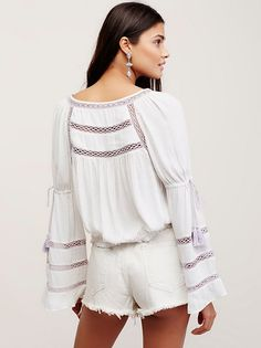 Take Me Home Peasant Top | Cropped to the natural waist this semi-sheer peasant top features contrast crochet trim throughout and boho inspired wide flared sleeves. Buttondown style with an elastic waistband for an easy fit.