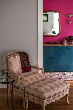The magenta wall isn't the only pink in Carla Caruso's home; the pom poms on the throw blanket add a good splash of color to the neutral chair. (From Sneak Peek: Best of Pinks and Reds) #sneakpeek #pink #red