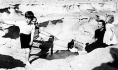 Charles and Anne watched over by their great Aunt and Uncle Earl and Countess Mountbatten as they play at Peters Pool beach during a trip to Malta 1954