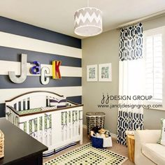 Navy blue and white stripes create a striking focal wall in this boy's nursery.