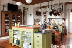 "Homeowner Craig Kettles painted his kitchen's island Bayberry Green from The Old Fashioned Milk Paint Co. Kettles chose green to incorporate the space into its natural surroundings. ""The house is on a lake, surrounded by trees, and it was a way of connecting the kitchen to the outdoors,"" he says. Iron rack with 12 votives by Jan Barboglio. Rhone pendant lights and Pacific City sconces above range from Rejuvenation. AeroTech wall oven by Fisher & Paykel."
