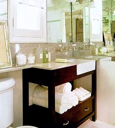 This table vanity outfitted with dramatic stain, a granite countertop, & an apron-front sink is wedged into a small corner with style. Partially open vanity below, offers shelf storage & makes area feel less cramped. A bottom drawer stores items best kept hidden, while the curvy wall-mount faucet saves space and adds panache. Could work in small bath.