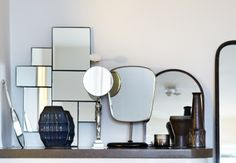 """Antique and modern mirrors installation on a mantle. From the left, handmirror by Nils Fougstedt for Herman Bergman´s Konstgjuteri, modern 7 mirrors and vase by House Doctor, """"Egypt"""" mirror by Svenskt Tenn, vintage shaving mirror, mirror fom the turn of the century around 1890-1900, candle holder Kastehelmi by Oiva Toikka, vintage vases. Picture from Elle Decoration."""