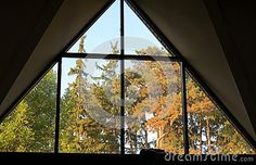 The late afternoon sun lights up the pine trees seen through a triangular-shaped window in a high ceiling.