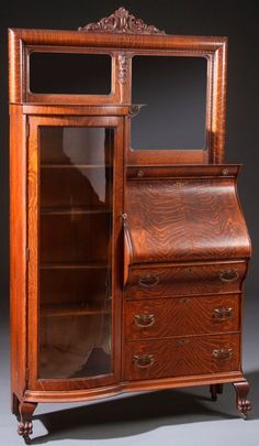 A VICTORIAN OAK SECRETARY BOOKCASE WITH DROP FRONT DESK SECTION AND BEVELED GLASS MIRROR, FLANKED ON THE LEFT WITH A CURVED GLASS VERTICAL BOOKCASE WITH FIVE SHELVES     CIRCA 1900