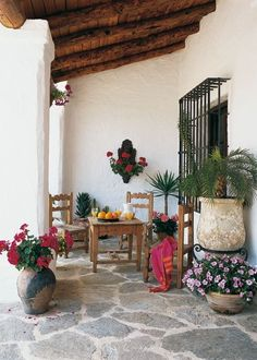 Spanish style porch with exposed wood beams, colorful potted plants and wrought iron window bars and plant stands.