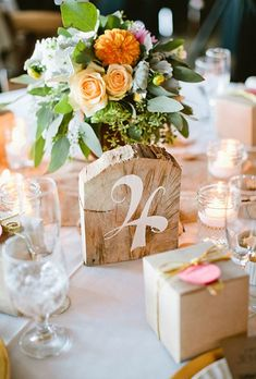 A rough-cut wooden table number with white writing.