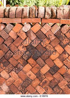 Old stacked red brick drystone garden wall in herringbone pattern - Stock Image