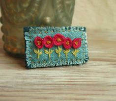 Pink and Teal Floral Embroidered Brooch Size: Just shy of 2 inches by 1 inch A row of bright pink ribbon flowers hand embroidered on teal linen Embroidery Stitches, Embroidery Patterns, Hand Embroidery, Flower Embroidery, Fabric Brooch, Felt Brooch, Textile Jewelry, Fabric Jewelry, Jewellery