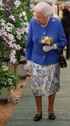 Queen Elizabeth dressed for the occasion in a blue and grey floral ensemble at the Chelsea Flower show. British Monarchy History, Hilarious Photos, Isabel Ii, House Of Windsor, Her Majesty The Queen, Chelsea Flower Show, Prince Philip, Queen B, Queen Elizabeth Ii