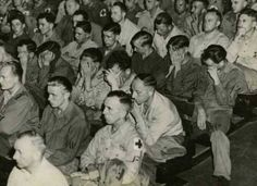 1945 – German POWs weep and sit in disgust as they watch footage shot at a German concentration camp.