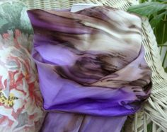 This gorgeous multi colored streaked scarf is hand painted and is 100% silk. Hand hemmed as well. Plum, Orchid, Orange, Fuchsia all intertwine to create a lovely combination of colors that will add rich jewel tones to your Autumn and Winter. Lovely mixture of colors dripping into each other to create a lovely picture for you to wear with your favorite outfit. This scarf is 11 x 58-60 (27.940 cm x 147.32cm-152.40 cm) and should be dry cleaned or hand washed in cold water. Low iron steam.  All…