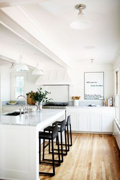 This white kitchen had us at hello,and then we saw the Andy Warhol print and died a little. In keeping with the home's heritage, Staton chose classic English shaker cabinets with wood knobs...