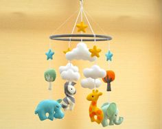 Welcome to FlossyTots This beautiful Animal mobile is MADE TO ORDER This colourful mobile consists of a Hippo, Elephant, Giraffe and Zebra in premium wool blend felt There is a cloud or tree above each animal and a coloured star above each of these, the hoop is decorated with grey felt. CUSTOMISE If you prefer you can choose your own colours of felt to match your nursery or bedding, just convo me to discuss! APPROXIMATE DIMENSIONS:- Wooden Hoop 10 Elephant 4.5 x 4.5 Hippo 4.5 x 4.5 Giraf...