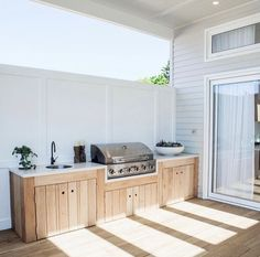 Outdoor grill with wood cabinet.