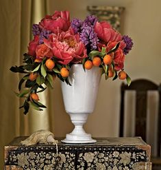 Outside the Flower Box This elegantly simple combination uses just three varieties, but adding stems of kumquats to the 'Coral Charm' peonies and hyacinths is an exciting and unexpected touch. In a footed urn with a wide mouth, it's best to let the flowers spill over.