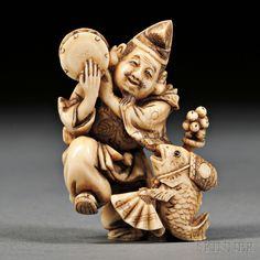 Ivory Netsuke of Ebisu, Japan, 19th century,  playing a Japanese drum over his right shoulder, dancing with a fish shaking a fan and bell, signed to base, ht. 1 5/8 in.