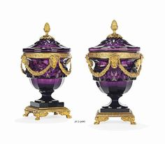 A PAIR OF RUSSIAN ORMOLU-MOUNTED AMETHYST GLASS BONBONNIERES SECOND HALF 19TH CENTURY Each of tapering form, the lid with pinecone finial, above a palmette and floral-cast rim adorned with swagged satyr masks, the facetted body with waisted socle, above a fluted square base with paw feet 10½ in. (27 cm.) high; 6 in. (15 cm.) diameter (2)
