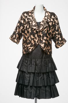 Dress by Gwen Gillam in black French silk taffeta with three-tiered skirt and self-tie belt. Theatre jacket in black and pale apricot silk brocade featuring dolman sleeves and a curved front opening.