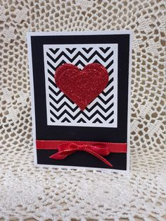 This Valentines Day card features a big red heart die cut from red glitter foam. The background is a white chevron panel on a black mat. The card is embellished with a red satin ribbon and bow. The inside of the card was left blank so you can add your own personal message. The card measures approximately 4 X 5 1/2. A white envelope is included.