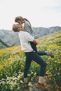 cute outdoor flower field engagement session but I don't like the guys outfit