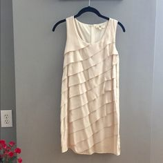 {Boutique} khaki colored dress Khaki colored dress with ruffles on the front, bought from a boutique a few years ago. Light weight, can be dressed up or down. Good for office attire  hits above the knees. Has a belt loop on each side if you want to add a belt, but comes with a matching cloth belt Dresses