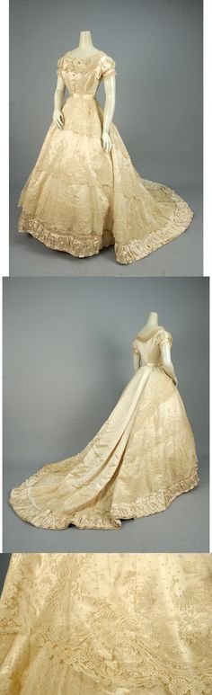 "PARIS LABEL SILK and LACE WEDDING DRESS, 1866. 2-piece ivory satin decorated with swags of lace on net, short sleeve bodice having self buttons and pleated tulle trim, trained skirt with wide pleated hem band. Petersham label ""Mon. Vignon 182. Rue de Rivoli Paris""."