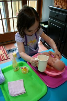 Plastic trays & tubs let kids mix water play & daily living role play while keeping the mess at a minimum.