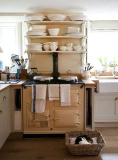 Love the white dishes on the shelf and the dog sleeping in the basket in front of cream Aga