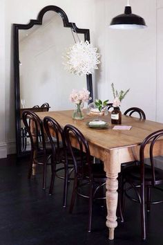 Chic dining room with black arched floor mirror at the end of the space reflecting the black enamel pendant hung over a rustic farmhouse dining table lined with Thonet Bentwood chairs atop black hardwood floors. Sala Grande, Bentwood Chairs, Metal Chairs, Black Chairs, Dining Room Inspiration, Design Inspiration, Table And Chairs, Room Chairs, Table Legs