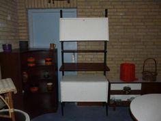 """Prachtig wall-system ontworpen in de jaren '50 door Louis van Teeffelen voor Webe. Dit wandsysteem is naar geheel eigen smaak in te delen. 2 zwarte houten staanders met een 2 deurs kastje, een klepkast met sleutel, 3 legplanken en een bureaublad en nog wat extra bevestigingsmaterialen. Schilderwerk is te verwijderen met afbijt voor fineer. Verkoophal """"ÚS Sporthal"""" Iedere Zaterdag van 11.00uur tot 17.00uur. Skrok 31/a, 8918 LA in Leeuwarden. Op een andere dag een kijkje nemen? Bel dan…"""