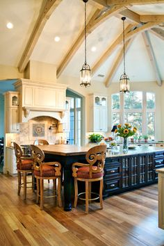Kitchen with beamed vaulted ceiling, tall windows, lantern lights, and large hearth. Hostetler Custom Cabinetry. Photo by Charleston Home and Design.
