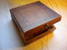 """ca. 1925-1930. This simple wooden box with a brass hook clasp is decorated in an Art Deco geometric pattern. The interior has the original yellow satin lining, and the underside is marked in pencil, """""""