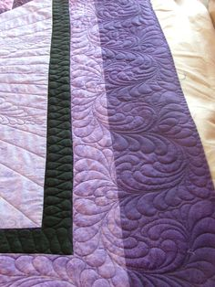 Amish curling feathers are great to unify multiple borders. Quilting by Deborah Poole