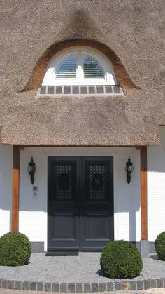 klassiek landhuis   een ruim gelegen rietgedekt landhuis van wit geschilderd metselwerk met karakteristieke ronde dakkapellen, stevige witte kozijnen en buitenluiken in een blauwgrijs kleuraccent