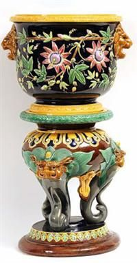 """A Brown Westhead & Moore Majolica Jardinière and Stand, the jardinière moulded with lion masks and twining foliage on a dark blue ground, the stand raised on three temple dog mask embossed supports, terminating in a spreading circular base (jardinière with extensive hairline cracks, stand with extensive repair to base), 31"""" high overall"""