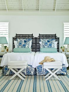 Outfitted with twin beds, lamps, side tables, and folding benches, this guest bedroom uses traditional blues and whites to create a soothing coastal space. Chocolate brown cane-and-rattan headboards add a graphic, tropical touch. (Photo: J. Savage Gibson)