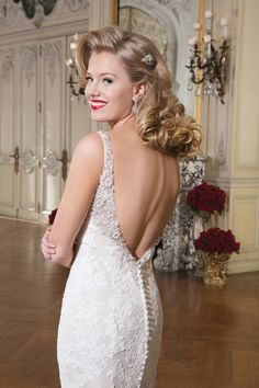 Style 8737 Alencon lace fit and flare gown with heavily beaded pearl and crystal V-neckline. The gown is finished with a plunging back neckline with matching beading, tulle covered buttons that cover zipper and a chapel train.