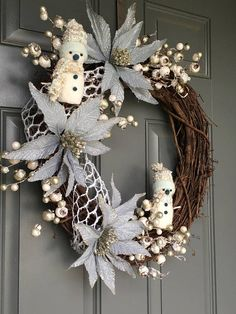 This Icy sliver blue winter wreath with snow covered berries and jolly snowmen will add an elegant yet playful touch to your winter front Door decor. This wreath features icy silver blue poinsettia flowers, snow covered berries thoughtfully placed throughout and two white and light