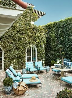A courtyard, framed by ficus hedges, makes a lush spot for relaxing or dining year-round. A straw tote is filled with sun hats; garden stools are used as both side tables and seating.
