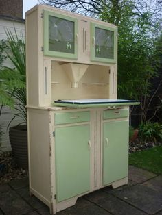 A fantastic vintage bakers cabinet. Painted in soft white and pale green... with glass front doors.