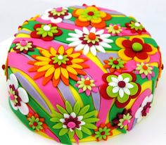 Bright and colorful flower cake. i would want the background chocolate. too, too much color here it think. it could definitely be toned down and still be whimsical and cute!