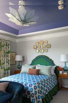 Interior designer Kim Alexandriuk used a striking palette, including gray, purple, blue, and green, in her daughter's Bel Air bedroom. A custom bed, linen curtains by Christopher Farr, Circa-1950 Murano glass lamps, and 1930s Italian tables are featured in the space. #kidsroom #teenroom